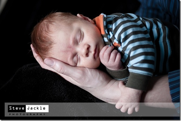 Campbell resting on the hands during his new born session - by Raleigh NC portrait Photographer Steve Jackle.