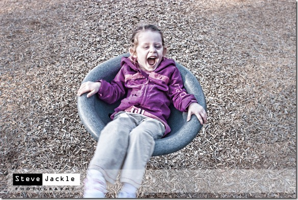 little girl smiling on the playground - kids lifestyle portrait photography by Raleigh photographer Steve Jackle