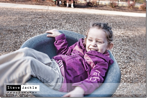 Spinning on the playground - kids lifestyle portrait photography by Raleigh photographer Steve Jackle