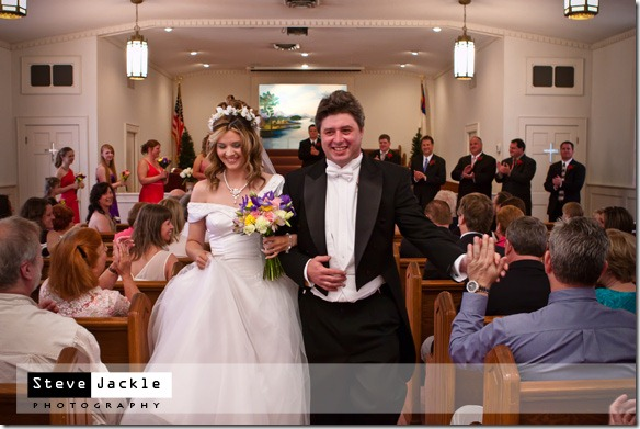 Husband/Groom gets high five when leaving the church at their wedding- photography by Steve Jackle Photography.