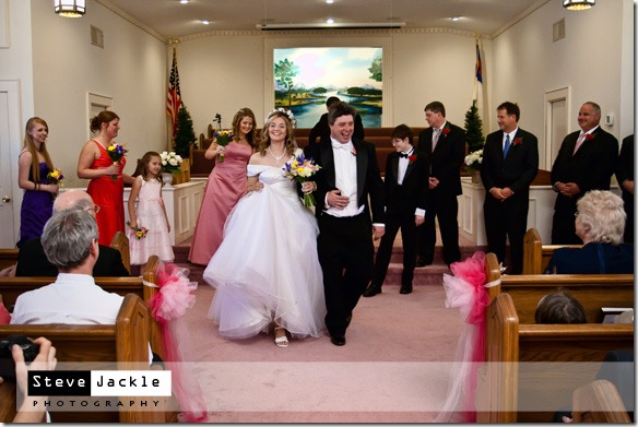 Husband and Wife proudly leaving the church at their wedding- photography by Steve Jackle Photography.